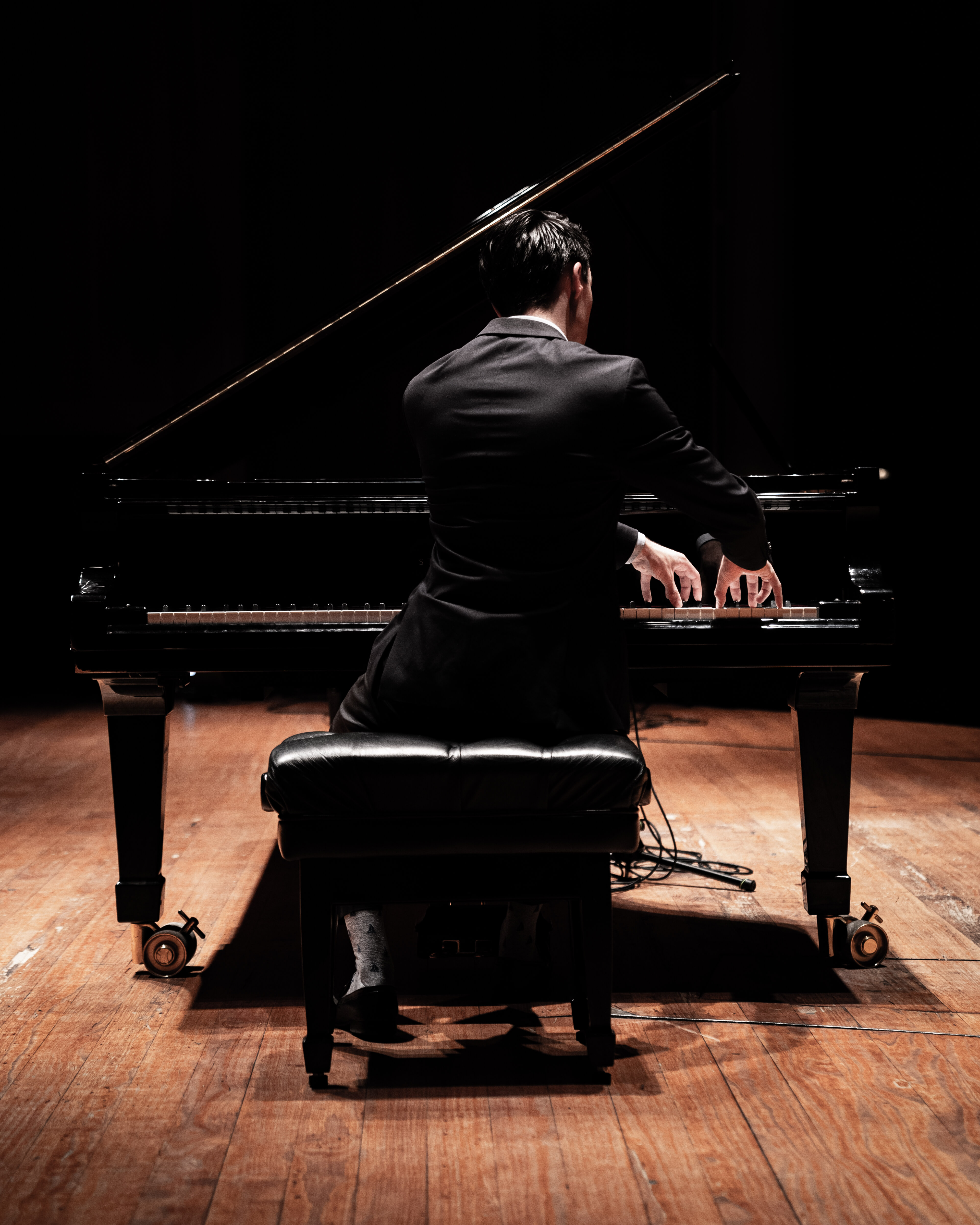 Pianist and grand piano and piano chair on a wooden floor with microphone cables.