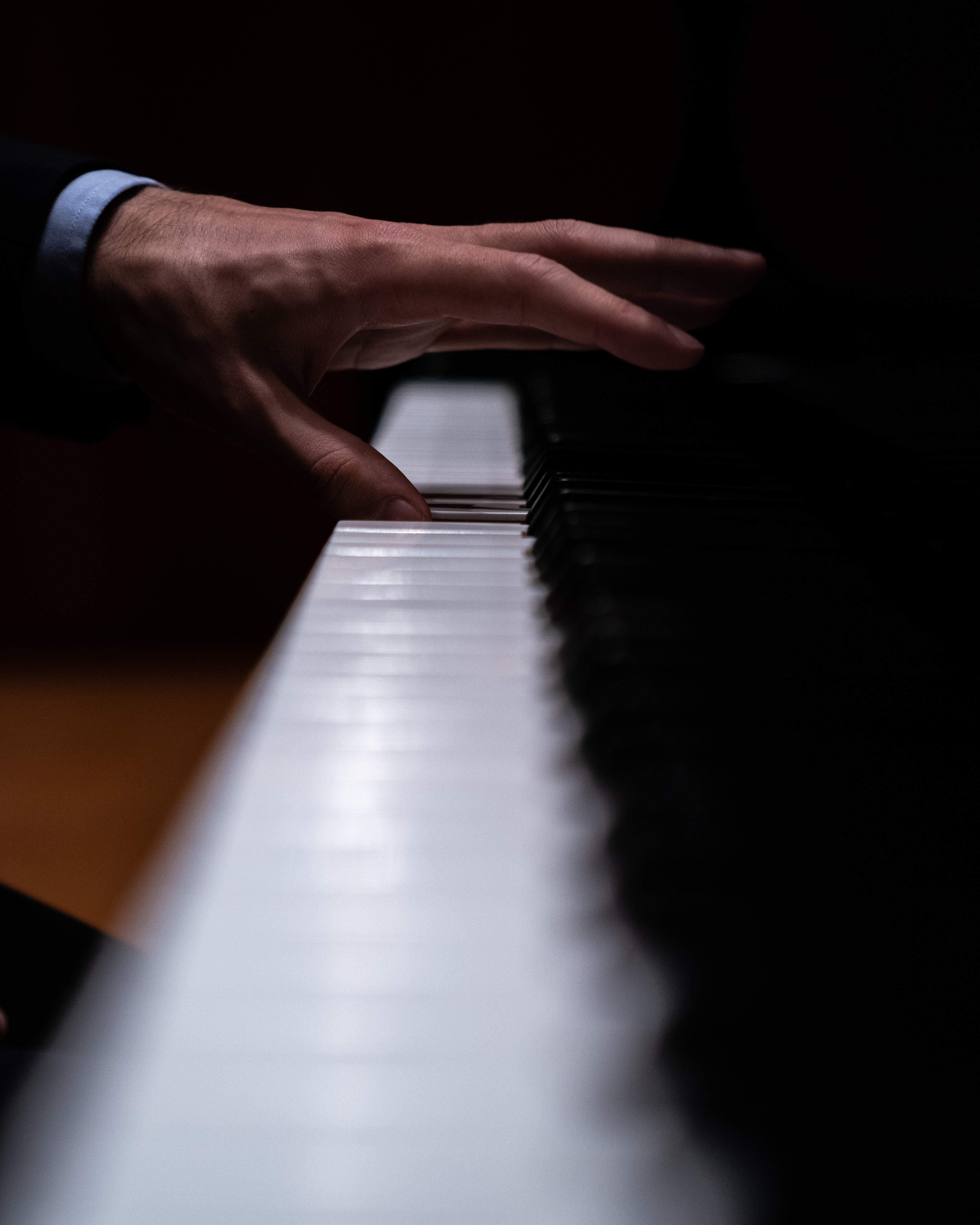 A single hand playing the beautiful black and white keys of a Steinway grand piano.