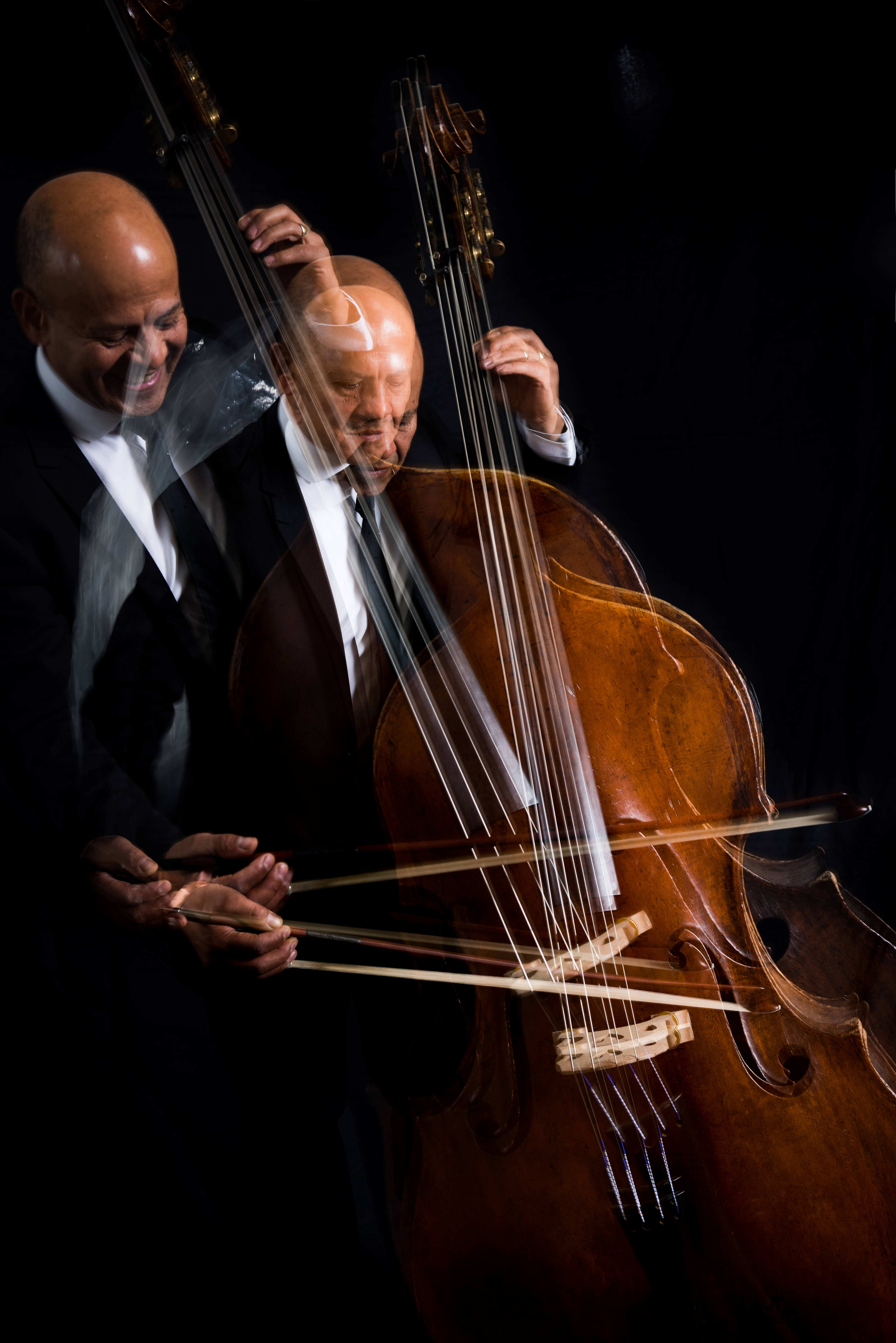 A mirror image of Leon Bosch playing a Double Bass in the dark.