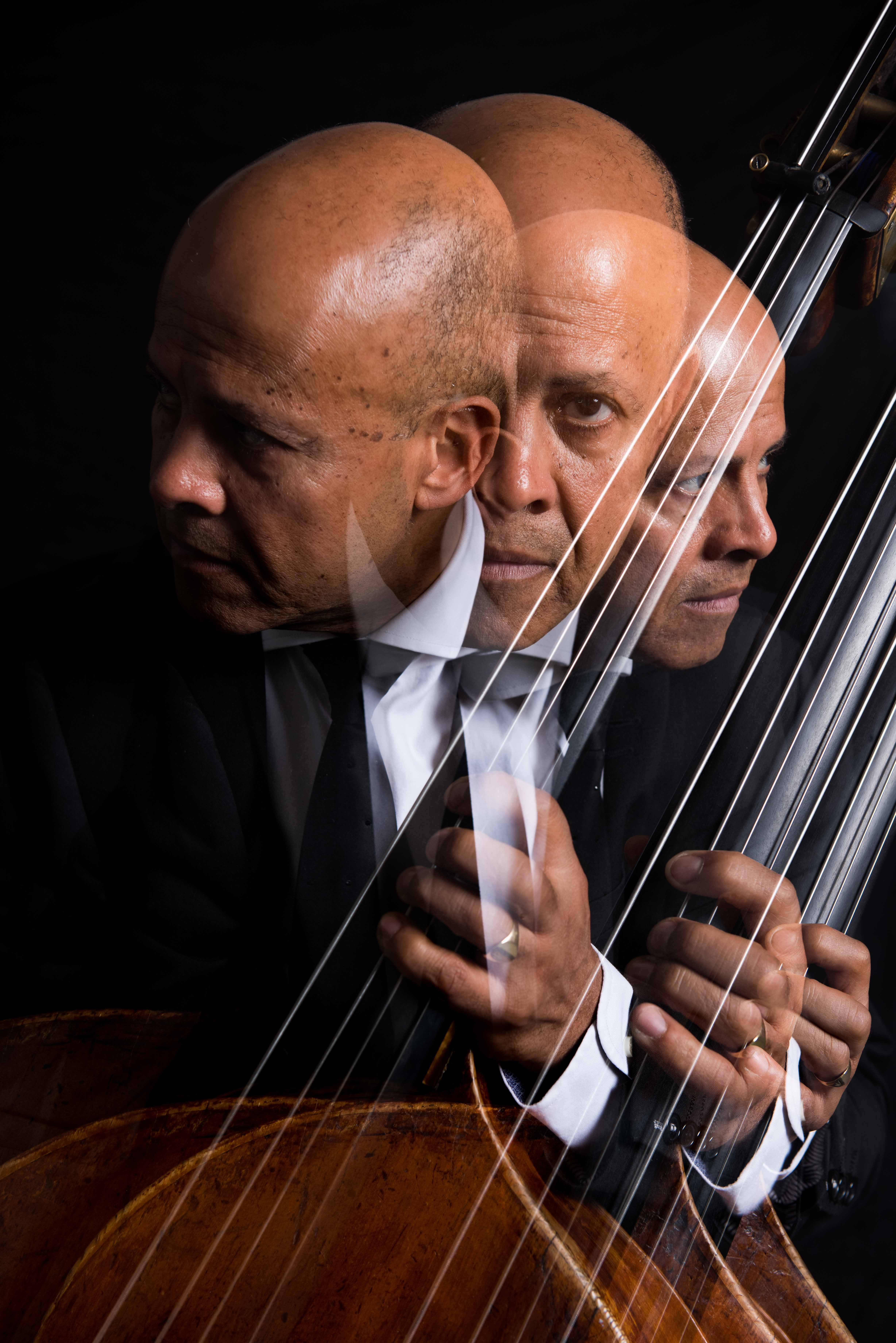 Leon Bosch and two mirror images of himself playing his double bass.