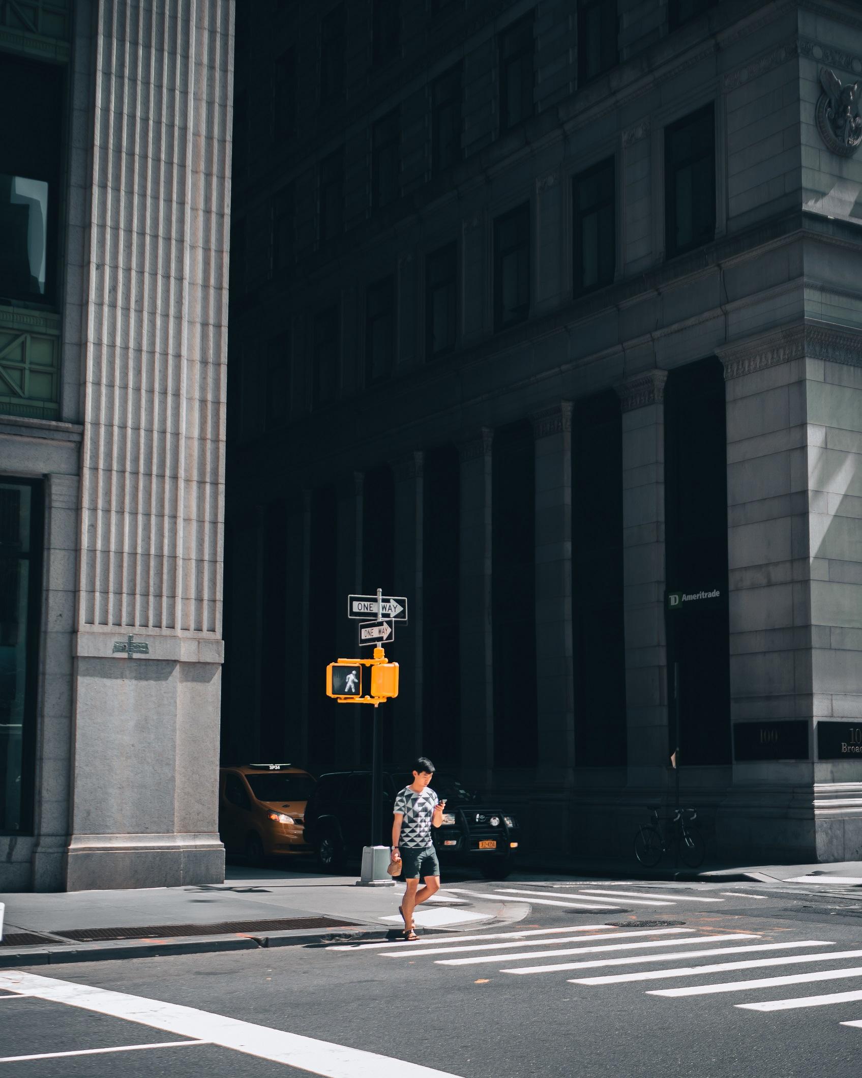 Man walking across the street in Wall Street, New York