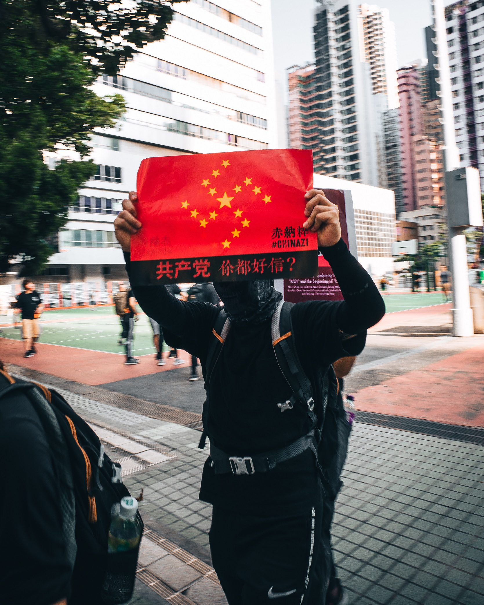 Male protester holding Chinazi protest sign