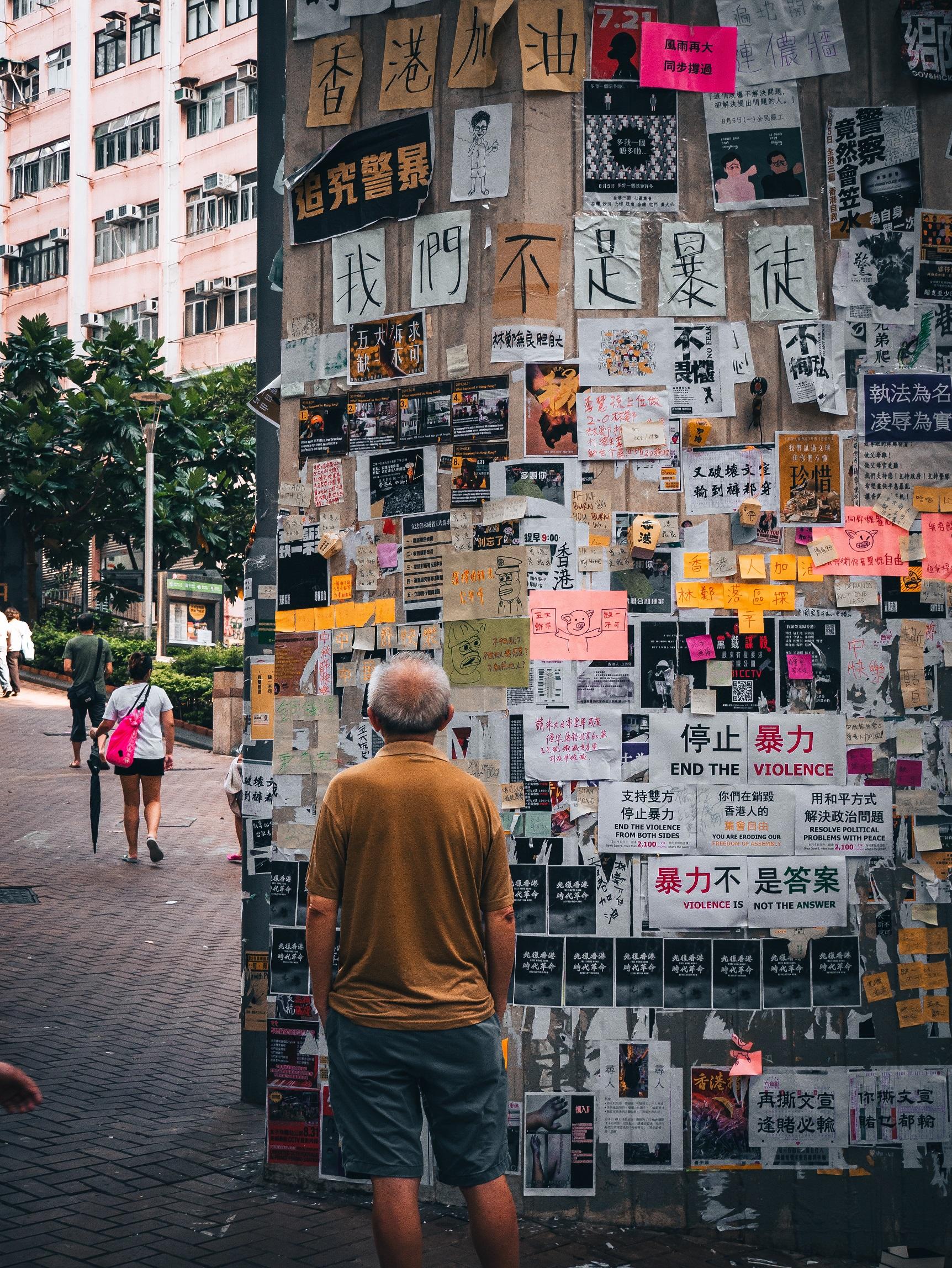 Man looking at Lennon Wall in Hong Kong