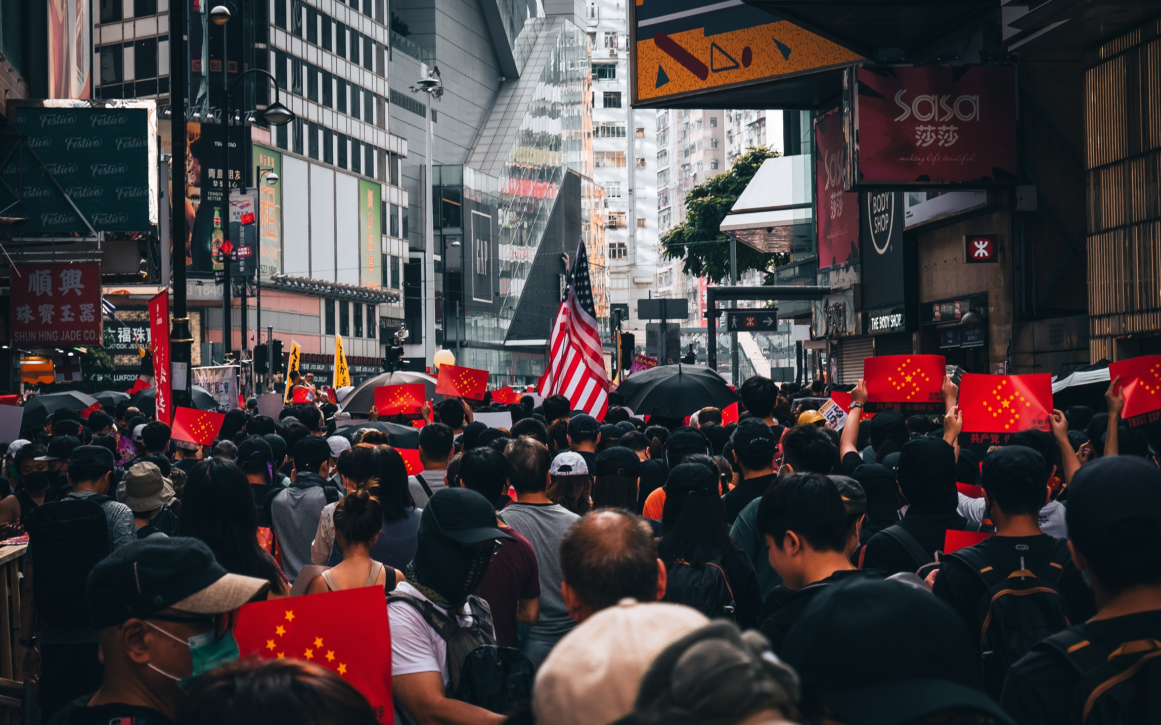 Protesters holding signs and American flag in Hong Kong