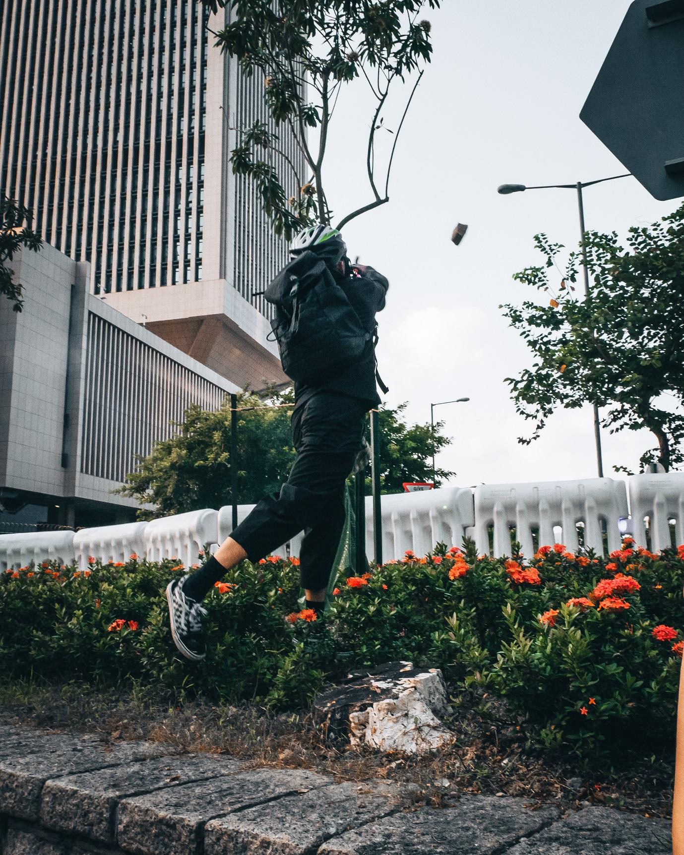 Protester throwing bricks at government building in Hong Kong