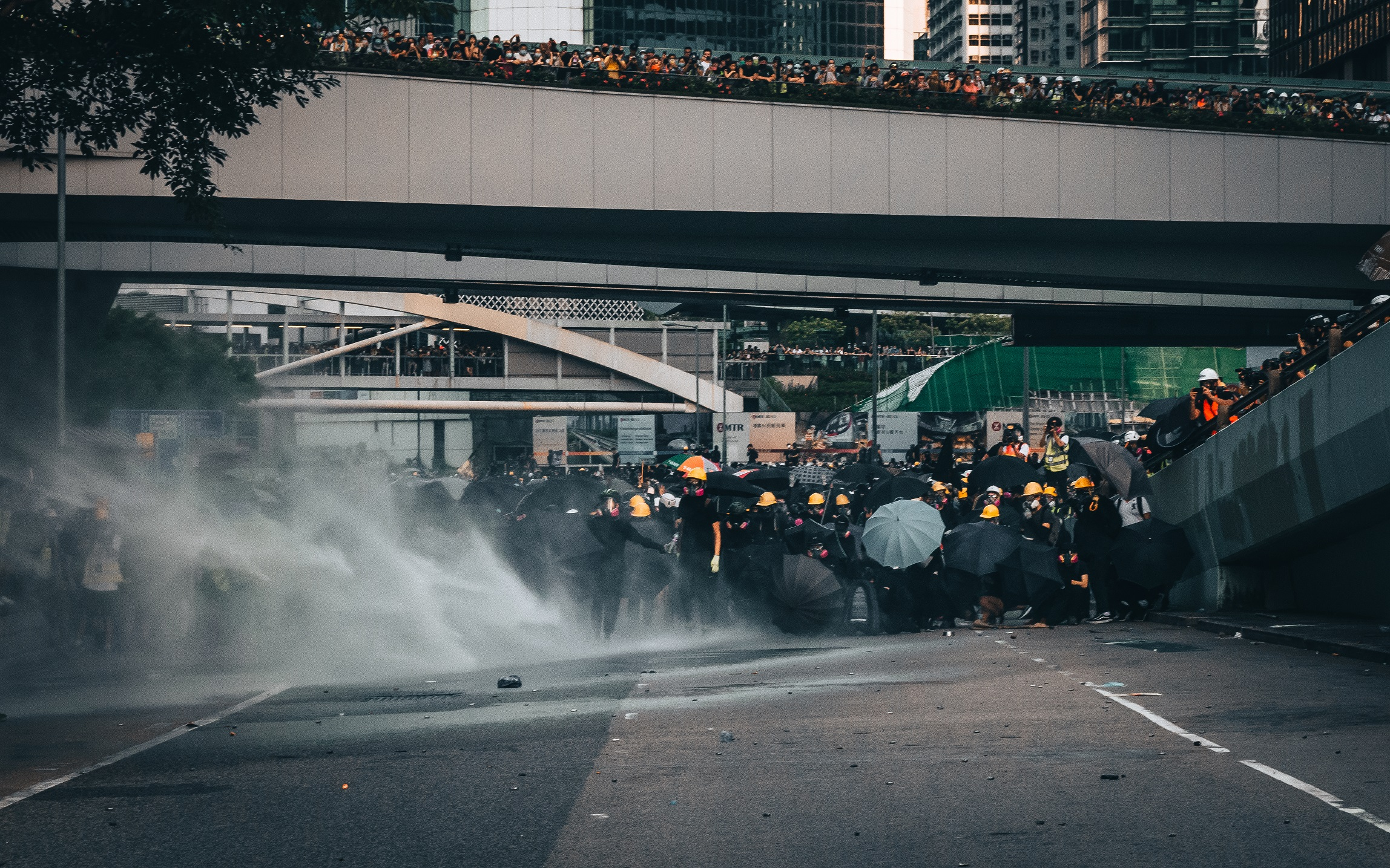 Hong Kong protesters forming an umbrella defense line to shield from water cannons