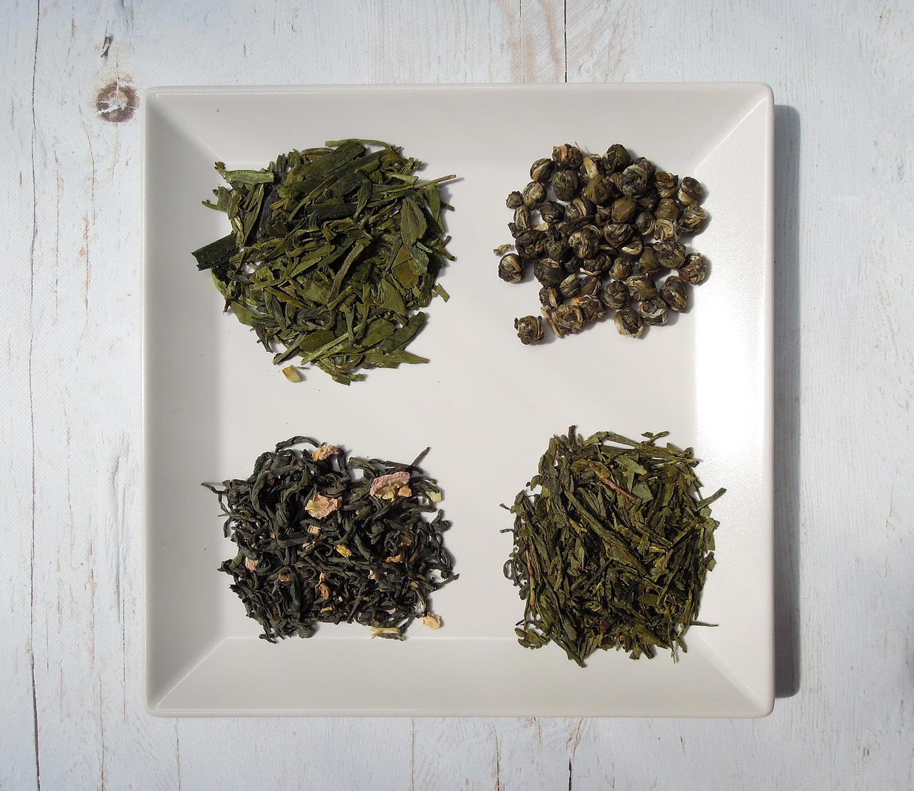 Green tea blends in dishes on a wood table