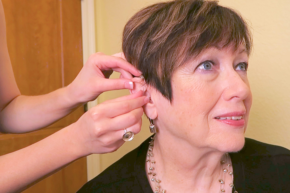 Female hearing loss patient being fitted for a new hearing aid.