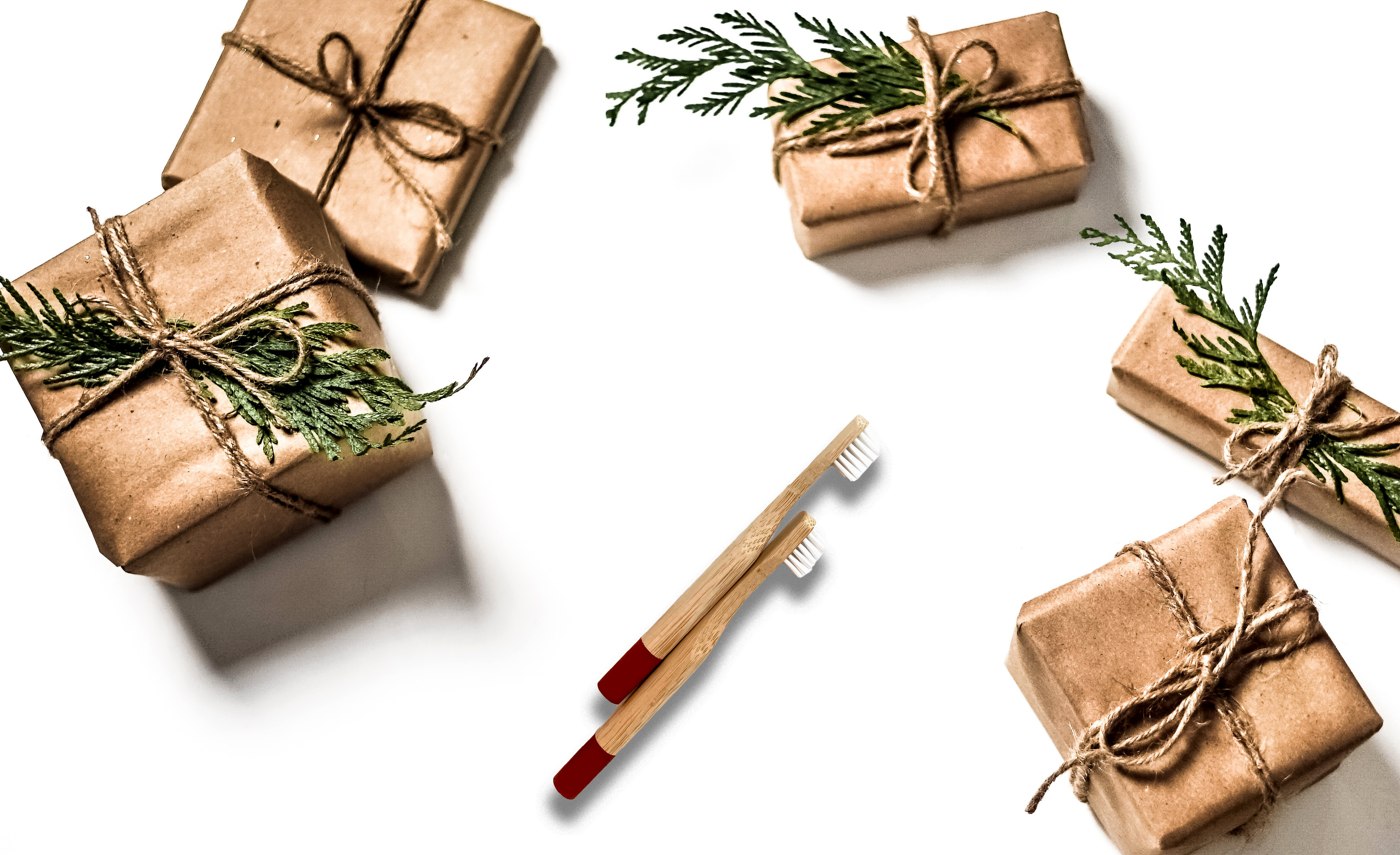 bamboo toothbrush surrounded by presents wrapped in kraft paper and tied with twine and pine boughs