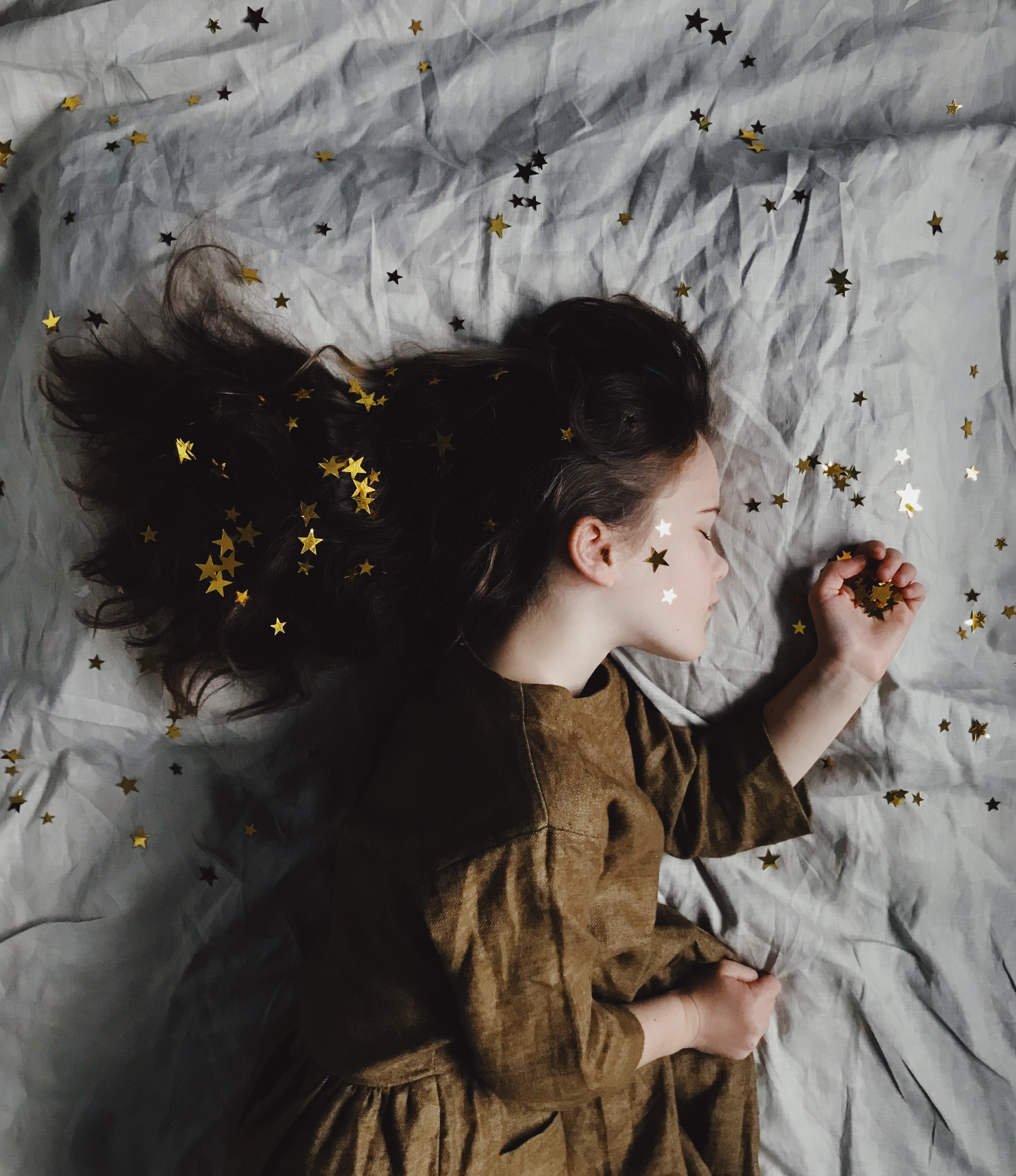 Young girl sleeping on a bed covered in stars