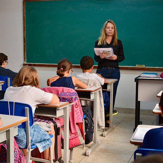 Professora em pé e segurando um caderno diante dos alunos que , sentados, fazem anotações.