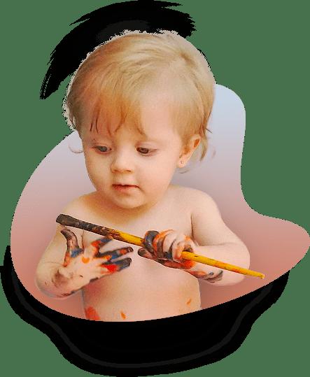Uma linda bebê loira pintando suas mãos com um pincel multicolorido.