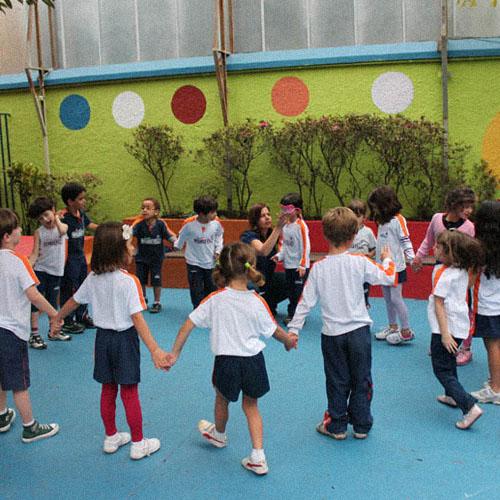 Crianças de 5 anos e uniformizadas brincando de ciranda.