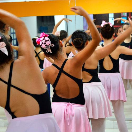 De costas, bailarinas-mirins usando collants pretos e saiotes rosas fazem pose com o braço direito curvado sobre a cabeça.