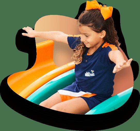 Menina de 7 anos, vestida com o uniforme da Escola Mundo Feliz, sorrindo e de braços abertos em um escorregador verde.