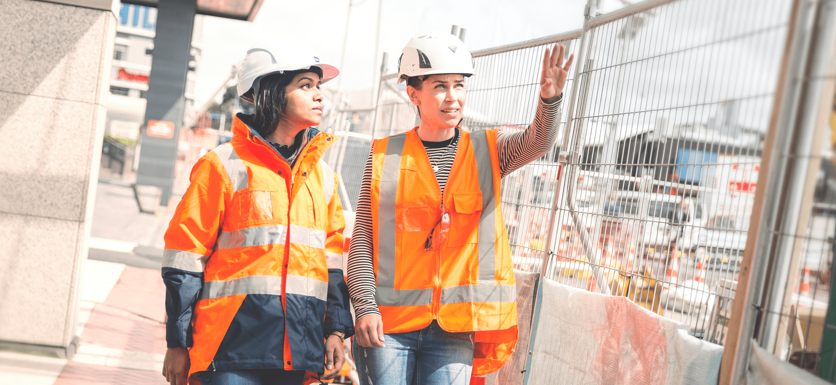 Two women in orange high vis jackets, and hard hats look at a construction site through a wire fence.