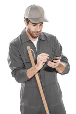 Ein Mann mit Smartphone und Besen in grauer Kleidung