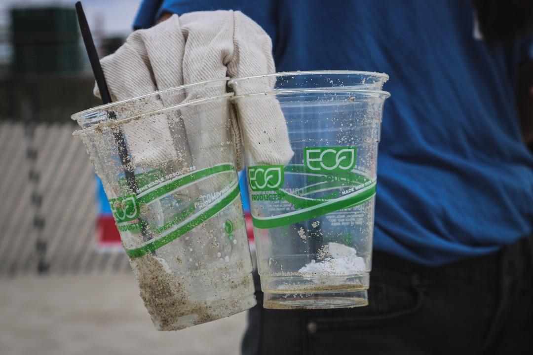 """Uma mão com luva segurando dois copos plásticos sujos de areia com a palavra """"eco"""" impressa em cada um deles"""