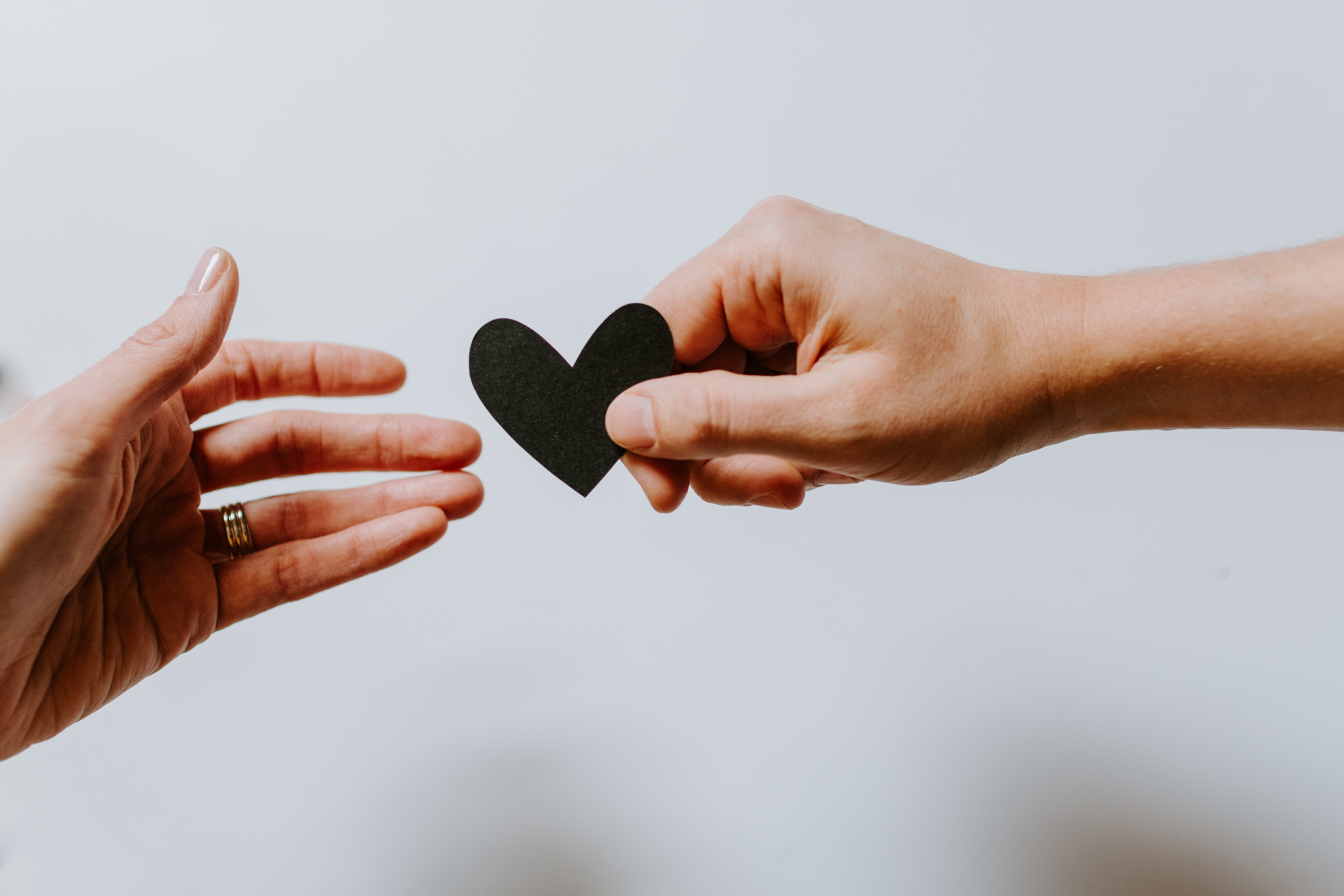 a hand gives a paper heart to another hand
