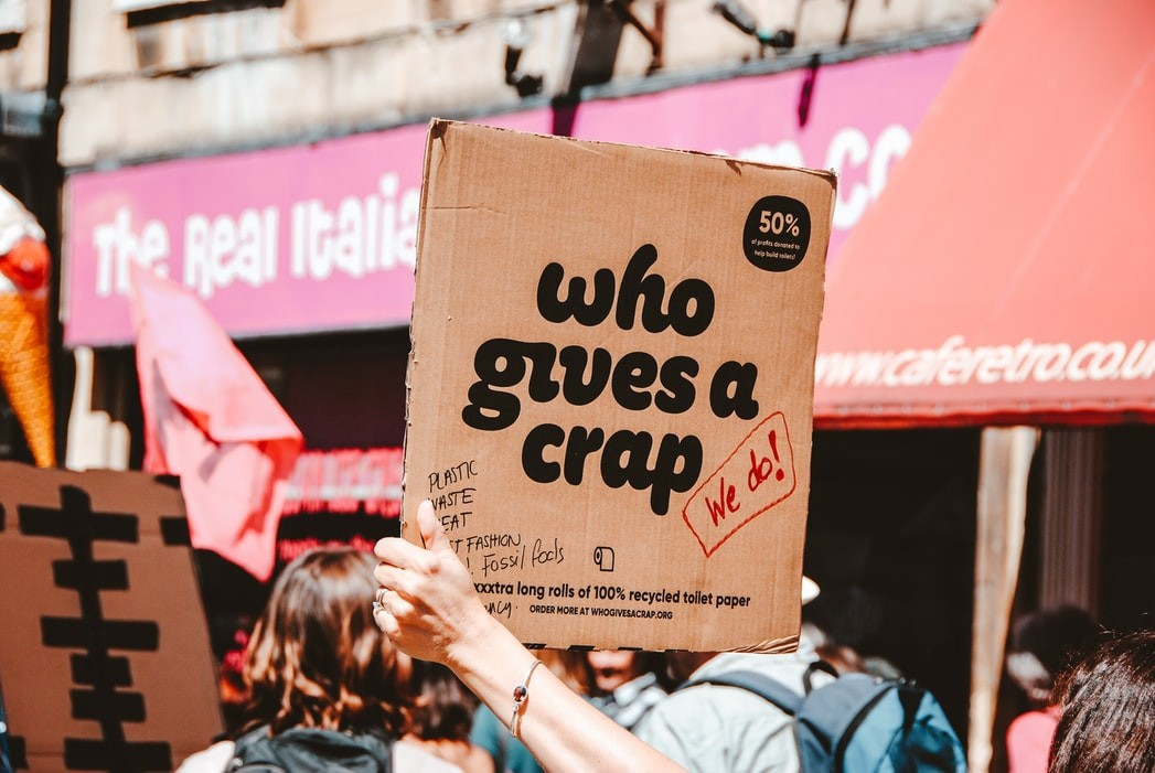 "Person holding a piece of cardboard where is written ""who give a crap""?"