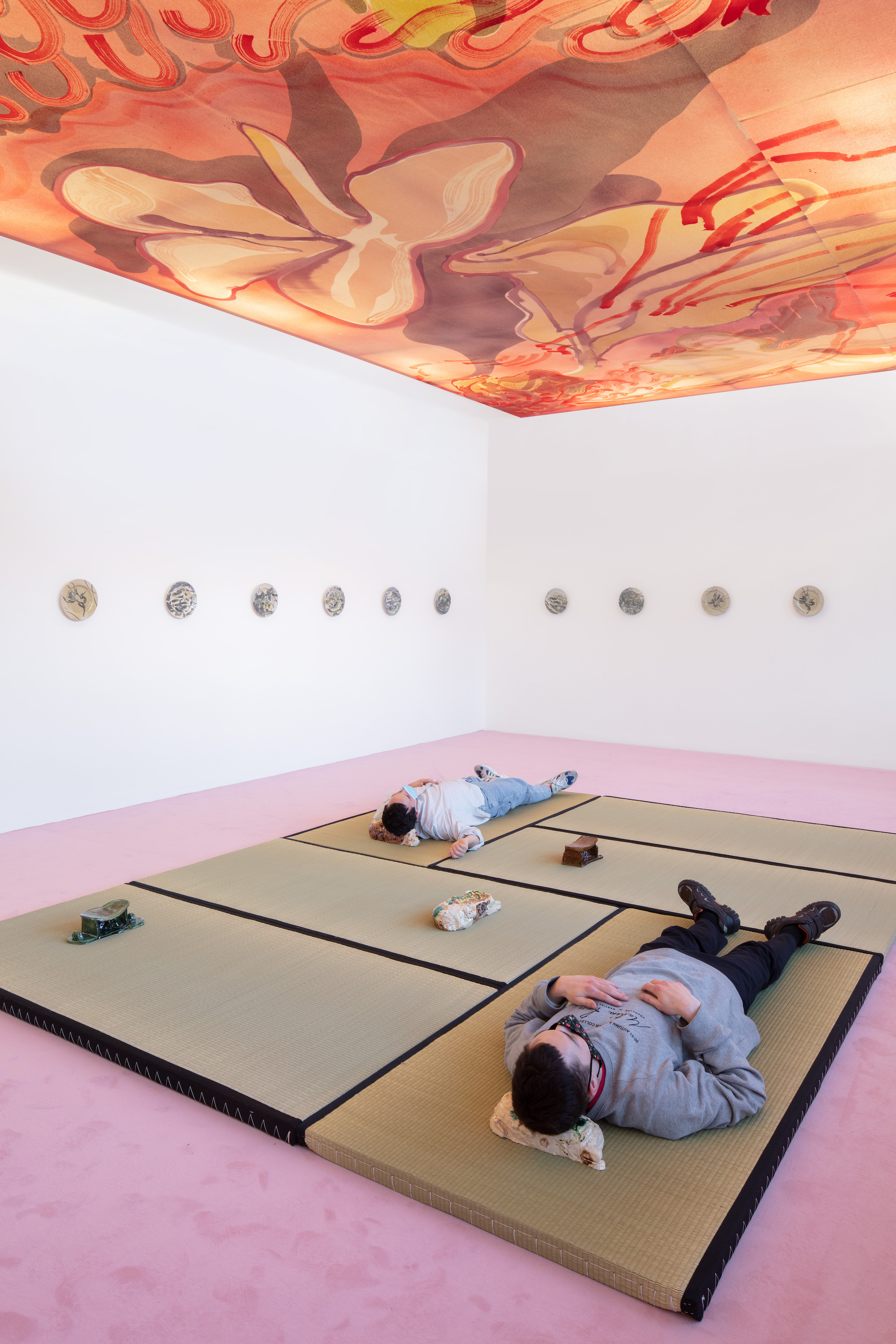 Installation view: Matthew Lutz-Kinoy. Window to the Clouds; Salon Berlin, Museum Frieder Burda Matthew Lutz-Kinoy, Wings of Flamingos, Camargue, 2020. Acrylic on canvas, 380 x 690 cm. Courtesy of the artist; Keramikos 3, 2019. Hand-painted set of 20 glazed ceramic plates. Courtesy of the artist and Mendes Wood DM São Paulo, New York and Brussels; Pillow In Cognac With Relaxed Figure, 2018; Pillow In The Form Of Reclining Child With Polkadots, 2018; Pillow In Green With Relaxing Figure, 2018; Pillow In The Form Of Reclining Child With Landscape, 2018; Pillow In The Form Of Reclining Child, Fishing Net, 2018. Glazed ceramics, dimensions variable. Courtesy of the artist and Fitzpatrick Gallery; Photo: Thomas Bruns