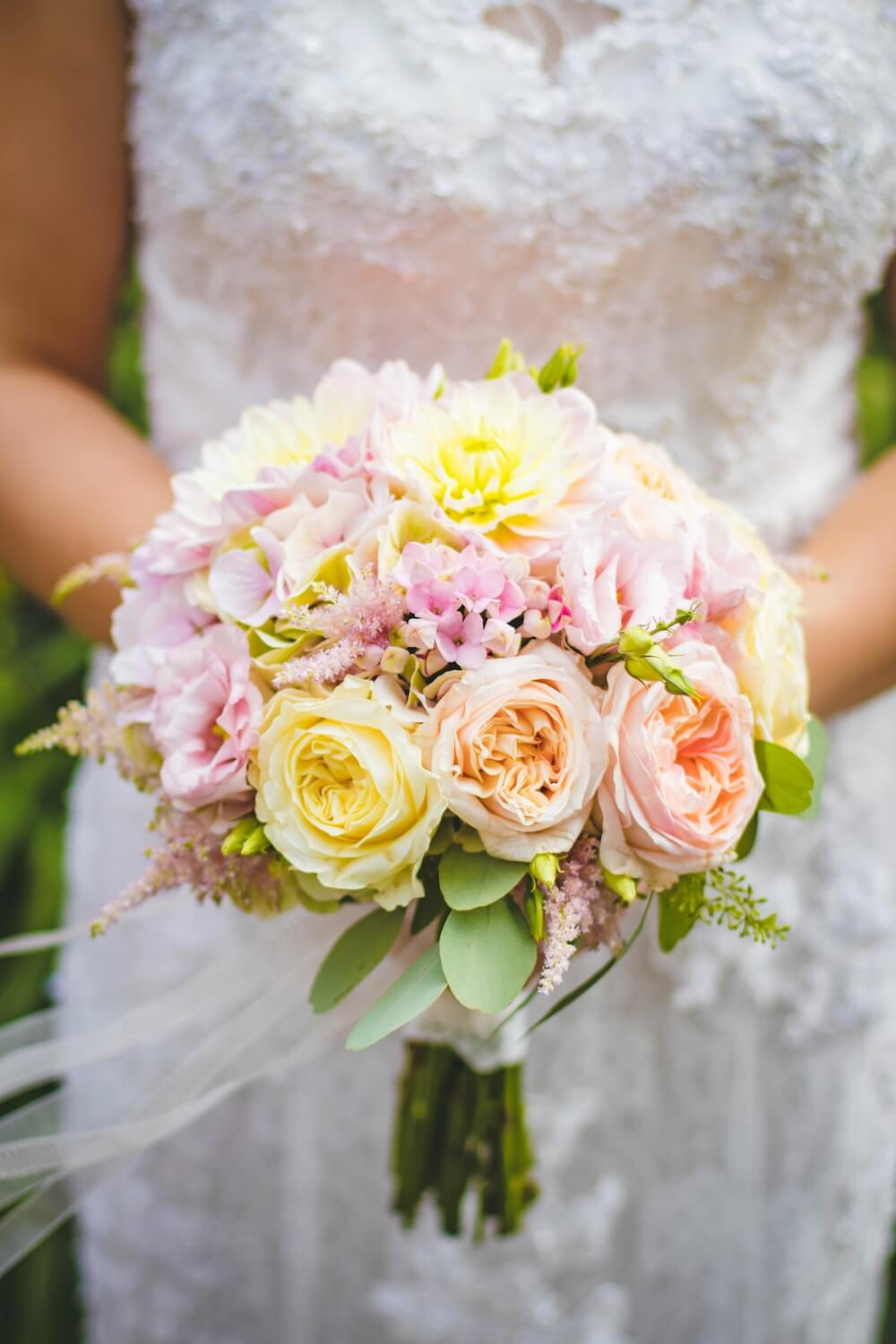Pastel flowers in a round bouquet held by woman in wedding dress