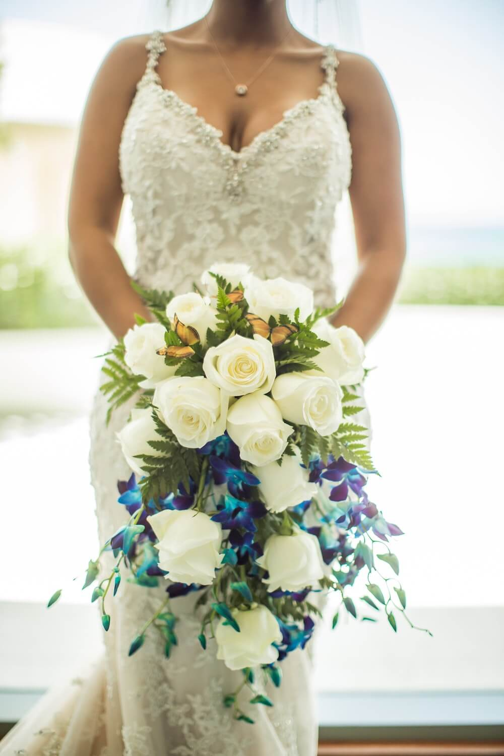 Blue and white flowers in a cascade bouquet held by woman in wedding dress