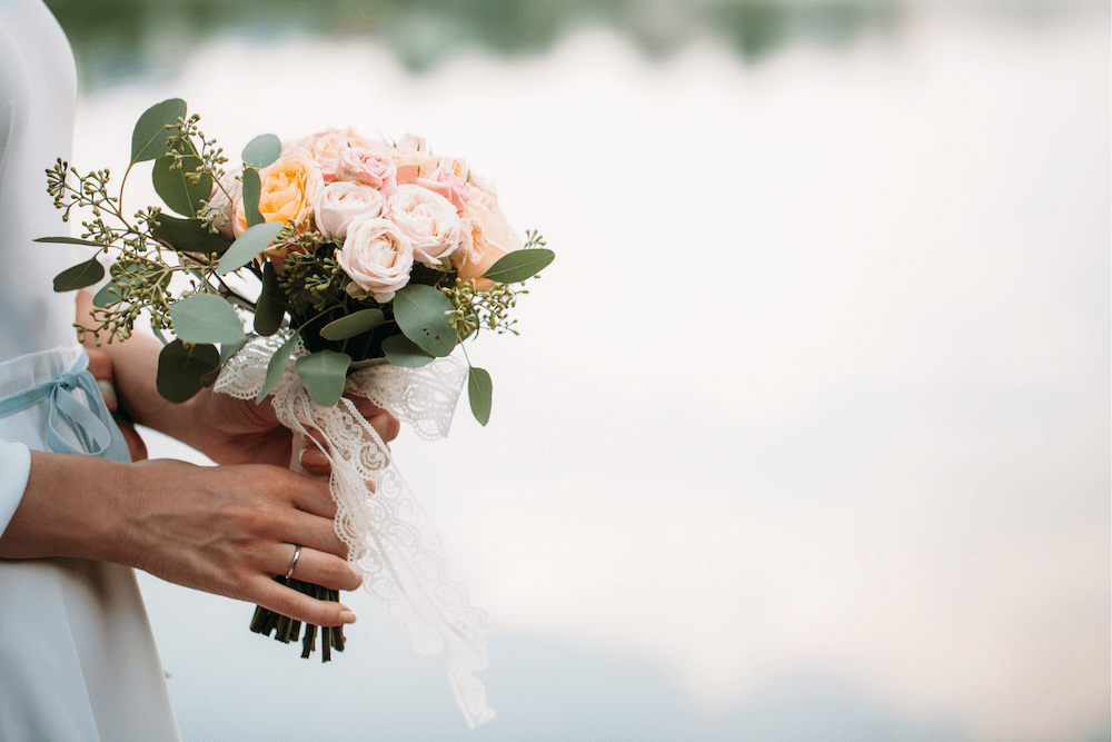 Pastel roses in a posy tied with ribbon held by woman in wedding dress
