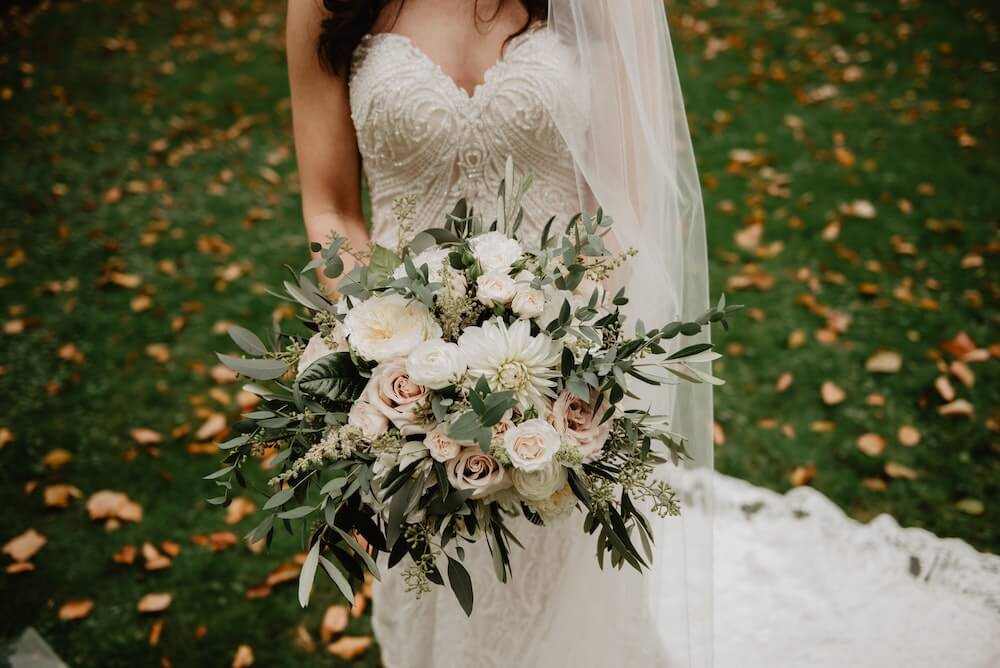 Flowers in a large bouquet held by woman in wedding dress