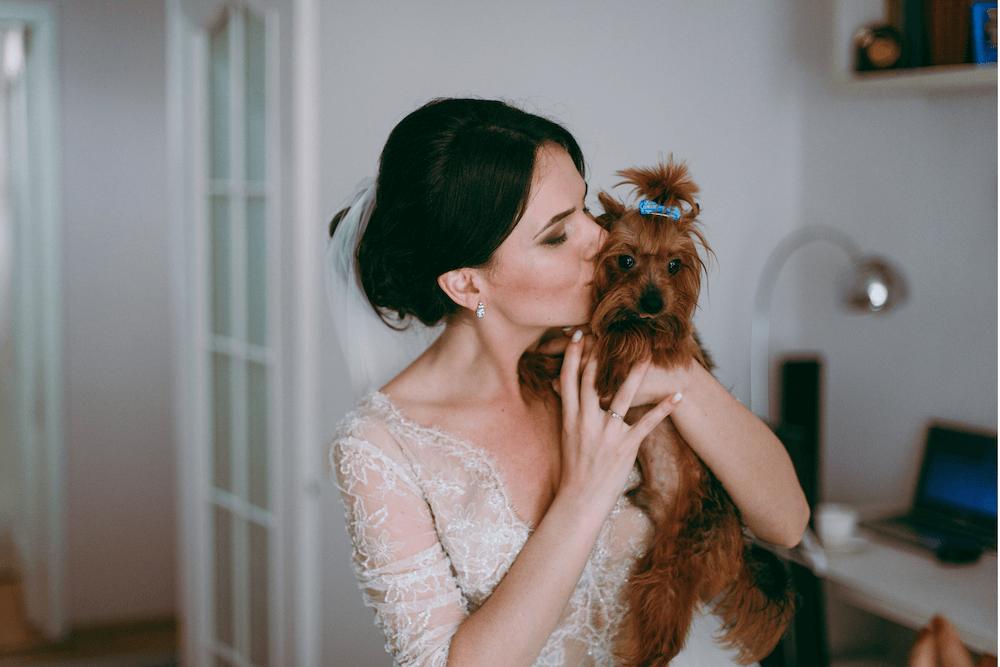 Woman in wedding dress kissing small dog