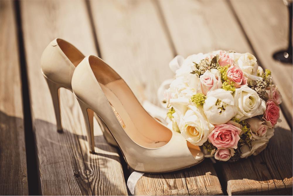 Round pomander bouquet sitting next to high heels