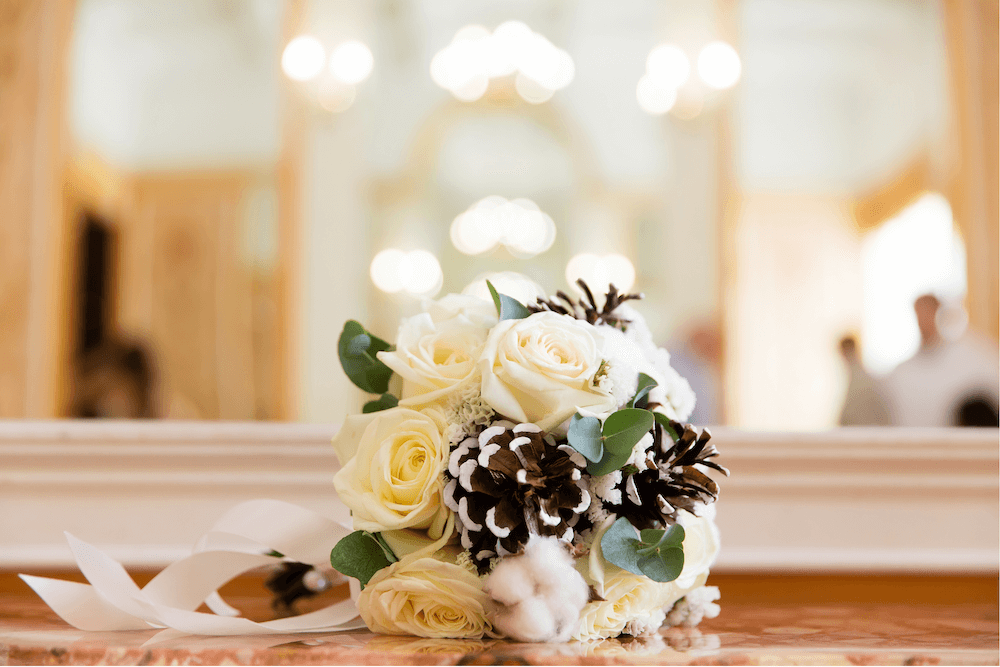 Small bouquet with white roses and pinecones lying on a table