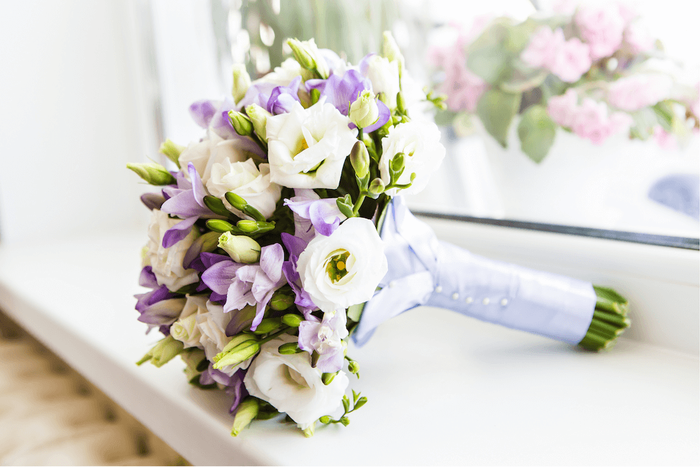 White and purple flowers in a bouquet tied with satin