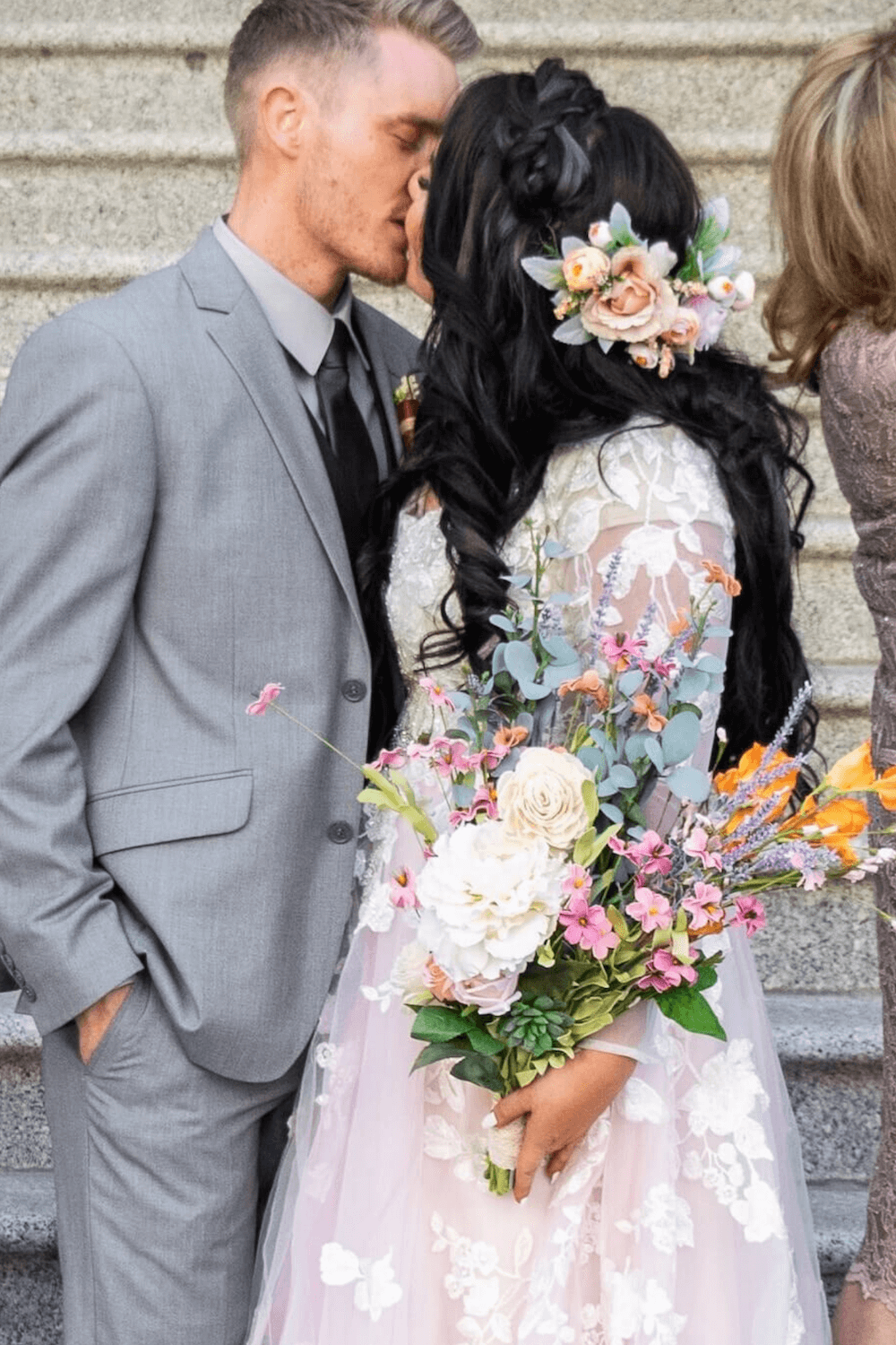 Large bouquet held by woman in wedding dress kissing man in grey suit