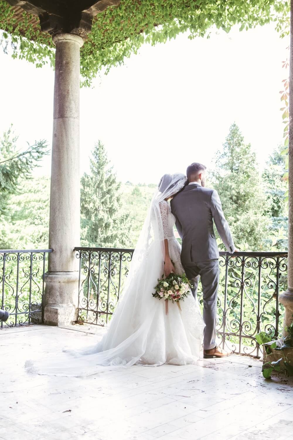 Bride and groom standing on terrace looking at trees