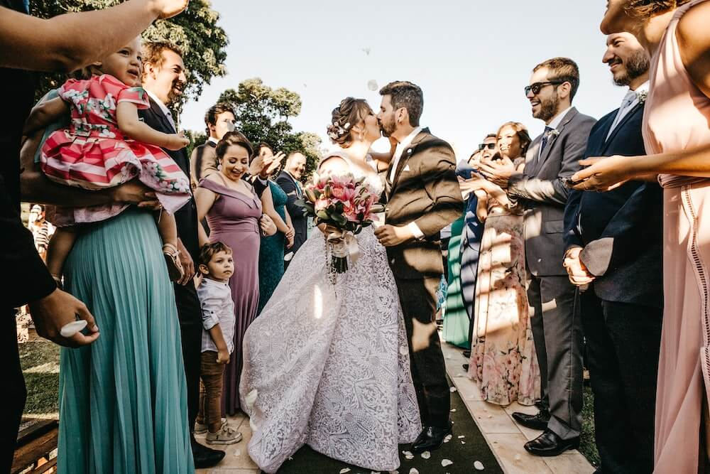 Bride holding bouquet kissing groom at wedding ceremony