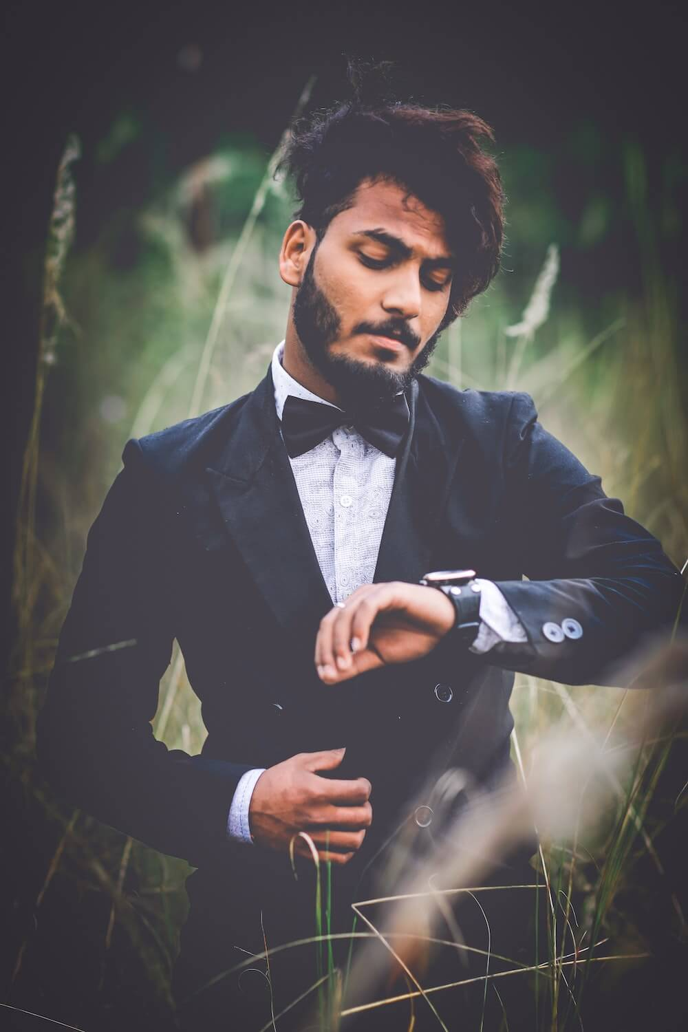 Man wearing suit looking at watch