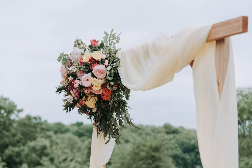 Colourful bunch of flowers attached to wooden arch