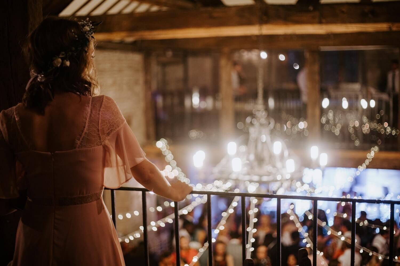 Bride Standing on Balcony Looking Over Wedding Guests Below