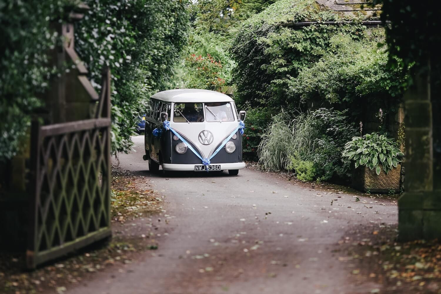 VW Kombi Dressed with Ribbons Driving Through Gates Carrying Bridal Party