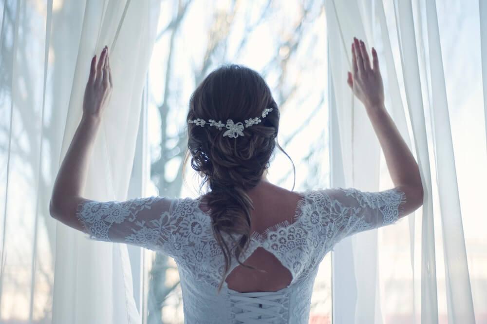 Woman opening curtains wearing wedding dress