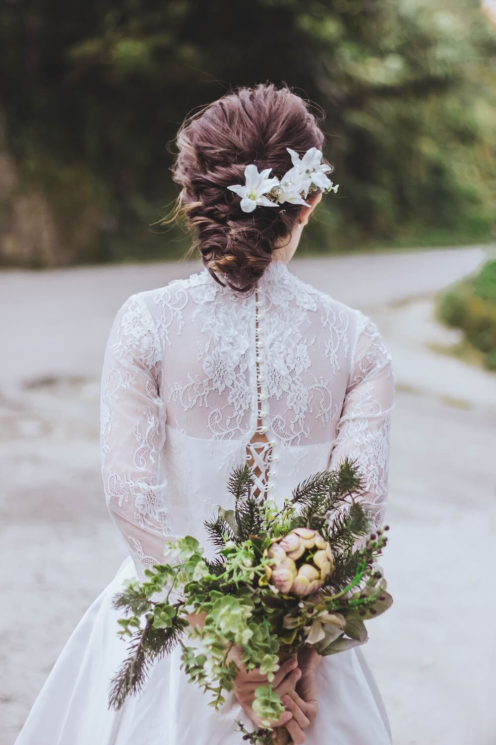 Woman holding wedding bouquet behind back