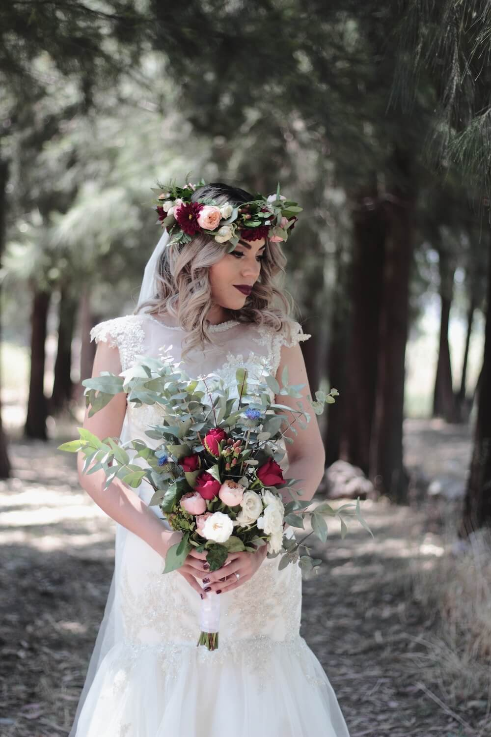 Woman wearing weddingdress and flower crown carrying large bouquet