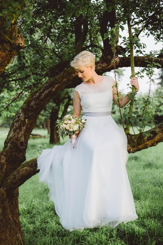 Woman sitting in tree wearing wedding dress