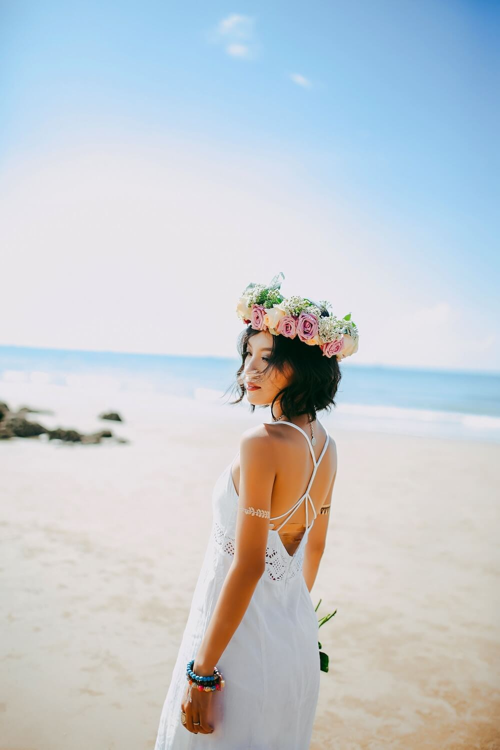 Woman standing on beach holding flowers