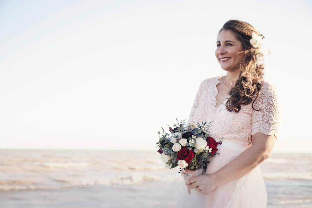 Woman smiling holding wedding bouquet on beach