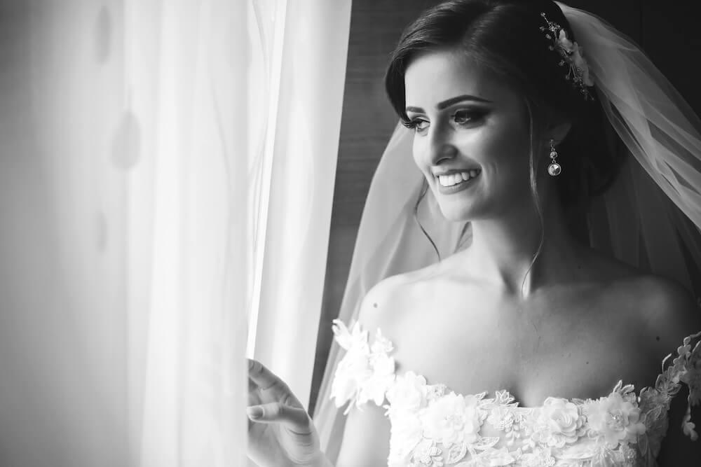 Woman wearing wedding dress pulling curtain open