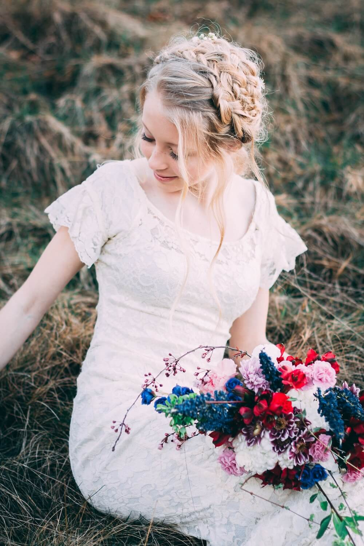 Woman sitting in grass wearing wedding dress