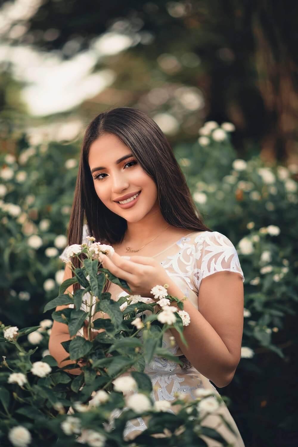 Woman wearing white dress touching flowers