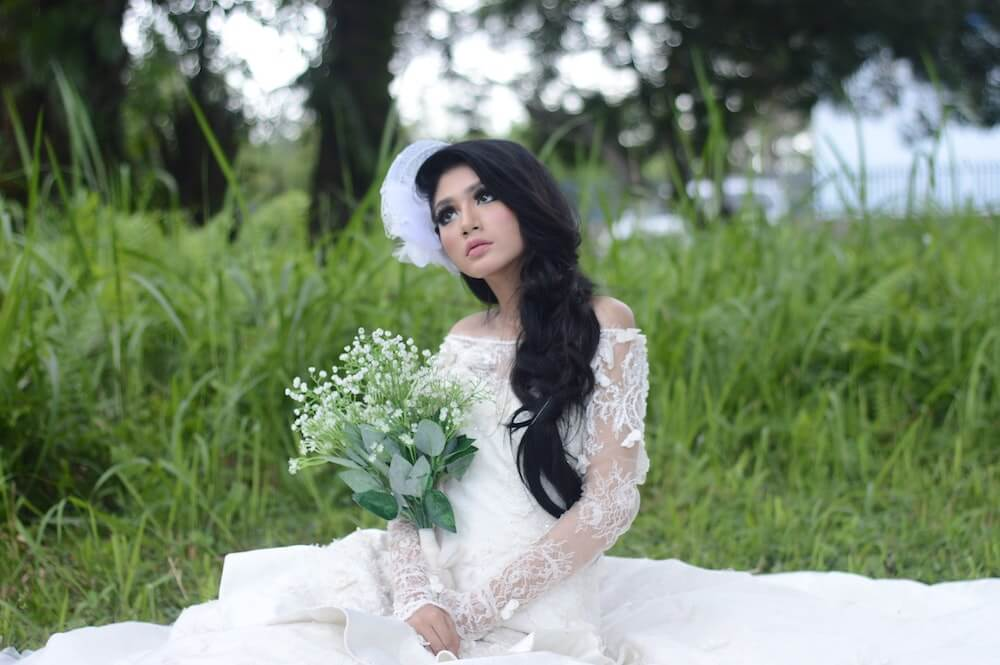Woman wearing white wedding dress sitting in grass